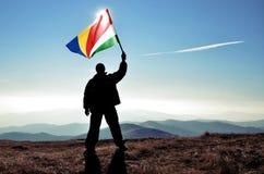 Ganador acertado del hombre de la silueta que agita la bandera de Seychelles encima de la montaña fotografía de archivo