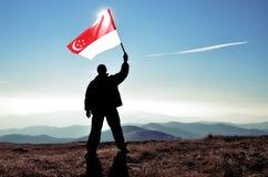 Ganador acertado del hombre de la silueta que agita la bandera de Singapur encima de la montaña fotos de archivo libres de regalías