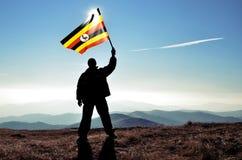 Ganador acertado del hombre de la silueta que agita la bandera de Uganda fotografía de archivo libre de regalías