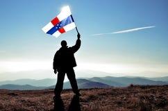 Ganador acertado del hombre de la silueta que agita Países Bajos Antillesflag encima de la montaña fotografía de archivo libre de regalías
