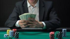 Ganador afortunado del casino que sostiene los billetes de banco del dólar, microprocesadores en la tabla alrededor, premio del j almacen de video