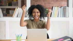 Ganador africano extático extático emocionado de la empresaria que celebra triunfo en línea foto de archivo libre de regalías