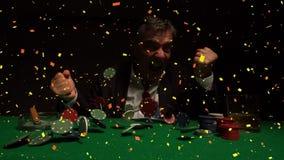 Ganador del casino que se sienta en la tabla del casino mientras que símbolos y confeti que caen en la tabla en la cámara lenta