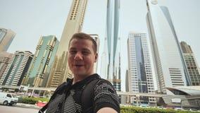 Ganador feliz del hombre contra el contexto de los rascacielos del ` s de Dubai almacen de metraje de vídeo