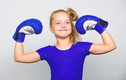 Ganador feliz del niño de la muchacha con los guantes de boxeo que presentan en fondo gris Ella siente como ganador Educación par imagen de archivo