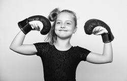 Ganador feliz del niño de la muchacha con los guantes de boxeo que presentan en fondo gris Ella siente como ganador Educación par imágenes de archivo libres de regalías