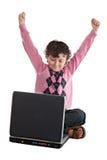 Ganador feliz del niño que se sienta con una computadora portátil imágenes de archivo libres de regalías