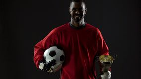 Ganador negro emocionado del fútbol que sostiene el premio y la bola, recompensa del deporte, felicidad metrajes