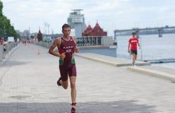 Ganador que corre en un terraplén de la ciudad durante del Triathlon 2019 de Dnipro ETU Junior European Cup imagen de archivo libre de regalías