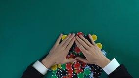Ganador que disfruta a todos los microprocesadores después de juego de póker, hombre codicioso que toma todo el dinero foto de archivo libre de regalías