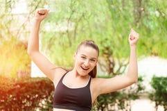 Ganando, concepto del éxito Hermosa, la muchacha del deporte de la aptitud disfruta en la victoria, aumenta sus manos para arriba Foto de archivo