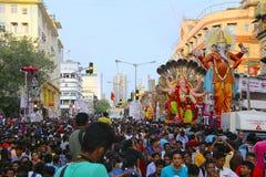 Ganapati procession med enorma Ganapati förebilder som bärs på lastbilar med fantaster royaltyfri bild