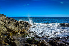 Ganaria di gran delle onde con le rocce e un uomo di pesca Fotografia Stock Libera da Diritti
