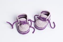 Ganchillo de los botines del bebé en el fondo blanco Fotografía de archivo