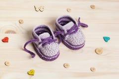 Ganchillo de los botines del bebé en fondo de madera Imagenes de archivo