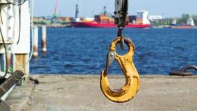 Gancho amarillo viejo de la grúa del primer en el puerto de envío sobre el mar, cantidad 4K almacen de metraje de vídeo