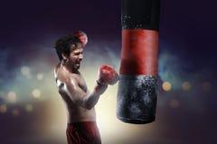Gancho asiático atlético del entrenamiento del boxeador con el saco de arena Fotografía de archivo