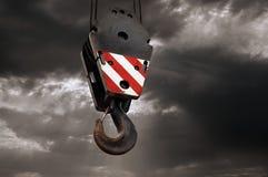 Gancho de leva de la grúa en un fondo dramático del cielo Imagenes de archivo