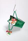 Gancho de pesca que sostiene un bolso verde con las medicinas Foto de archivo