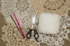 Ganchos de ganchillo en el fondo de lino con el tapetito/el cordón del ganchillo Fotografía de archivo libre de regalías