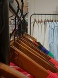 Ganchos de roupa arranjados ordenadamente na loja de roupa imagens de stock royalty free