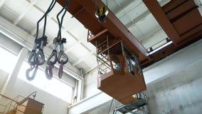 Ganchos que cuelgan en la grúa del haz de la fábrica en la planta Trabajo en el almacén del metal, transporte de productos metrajes