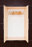 Ganci di cappotto di legno sulla ferrovia dei vestiti nel gabinetto Immagine Stock Libera da Diritti