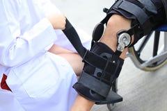 Ganci di ginocchio della riparazione del fisioterapista della gamba dell'uomo senior con la seduta sulla sedia a rotelle, sul con immagini stock