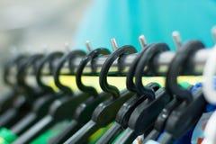 Ganci di plastica con i vestiti nel deposito Fotografia Stock