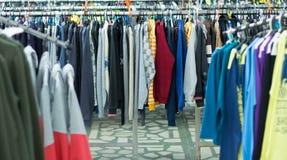 Ganci di plastica con i vestiti nel deposito Fotografie Stock