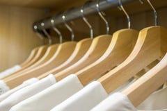 Ganci in una fila con le camice bianche Fotografia Stock