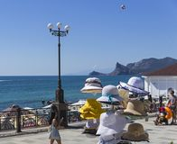 Gancio con i cappelli femminili di estate nel deposito sul lungomare Fotografie Stock Libere da Diritti