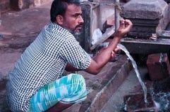 Gandhinagar, Gujrat, Inde en mai 2018 - photo de plan rapproch? des mains de lavage de l'homme avec de l'eau de tuyau pr?s de rou photos libres de droits
