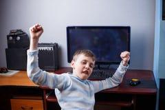 Gane el juego Muchacho emocionado feliz que juega al juego de ordenador en su roo Imágenes de archivo libres de regalías