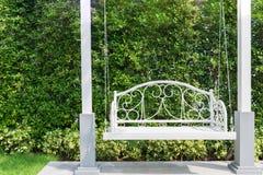 Ganek frontowy z białą ganeczek huśtawką przy ogródem w domu fotografia stock