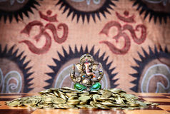 Ganesh on heap of coins. Little statue of ganesh in green trousers sitting on the heap of golden coins on chess desk at om signs background Royalty Free Stock Photo