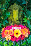 Ganesh statue with hibiscus flowers, Thailand. Ganesh stone statue with hibiscus flowers, Thailand Stock Photos