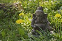 Ganesha石头雕象在一个绿色庭院里 图库摄影