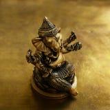 Ganesha bronze figurine over golden background Royalty Free Stock Photo