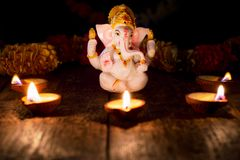 Ganesha with Diwali lights. Ganesh Chaturthi or Diwali concept - Ganesha figurine with Diwali lights oil ghee candles, India stock images