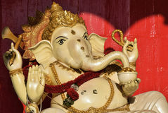 Ganesha (Phra Phikhanet). Statue in Thai Wat with red background. Holding weapons in hands and snacks in trunk. Bejeweled in gold and red flowers Royalty Free Stock Image