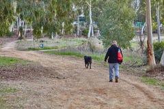 Ganey Aviv - 2. Dezember 2016: Ein Mann geht mit seinem Hund im f stockfoto