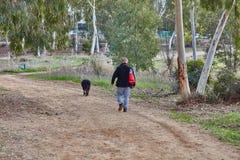 Ganey Aviv - 02 2016 Grudzień: Mężczyzna chodzi z jego psem w f Zdjęcia Royalty Free