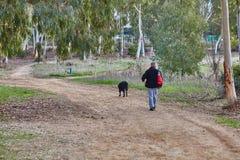 Ganey Aviv - 02 2016 Grudzień: Mężczyzna chodzi z jego psem w f Fotografia Stock