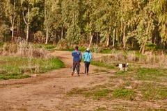 Ganey Aviv - 02 2016 Grudzień: Para chodzi z ich psami wewnątrz Obrazy Stock