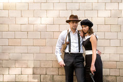 Gang. Young couple with guns dressed as 30-s mobsters Royalty Free Stock Photo