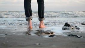 Gang blootvoets langs de zandige kust van het de winteroverzees stock footage