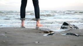Gang blootvoets langs de zandige kust van het de winteroverzees stock videobeelden