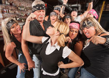 Gang Cheering On Nerd Flexing. Biker gang cheering on skinny female nerd flexing muscles Stock Images