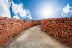 Gang door bakstenen muren met hemel royalty-vrije stock foto